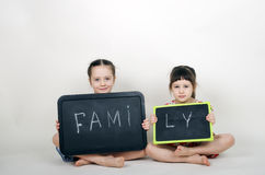 Little cute girls hold a board with the word Family Royalty Free Stock Photography
