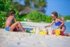 Little cute girls playing with beach toys during Stock Images