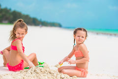 Little cute girls playing with beach toys during tropical vacation Royalty Free Stock Image