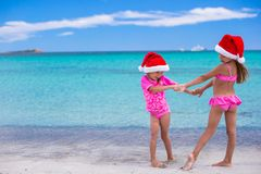 Little cute girls in Santa hats having fun on Stock Images