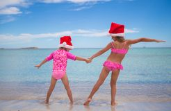 Little cute girls in Santa hats having fun  Royalty Free Stock Images