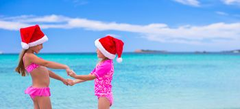 Little cute girls in Santa hats during summer Stock Photo