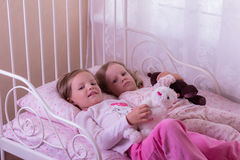 Little cute girls (sisters) play in bed. Royalty Free Stock Photography