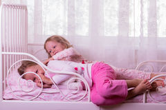 Little cute girls (sisters) play in bed. Royalty Free Stock Photos