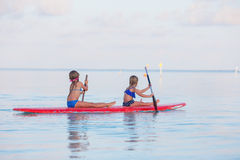 Little cute girls swimming on surfboard during Royalty Free Stock Photos