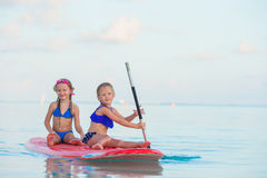 Little cute girls swimming on surfboard during Stock Images