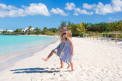 Little cute girls walking along the white beach Stock Image