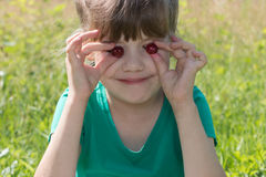 Little cute gitl holds two cherries at summer day outdoor, Stock Photography