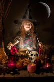 Little cute halloween witch reading spell above pot. Halloween. cheerful little witch with a magic wand Royalty Free Stock Image