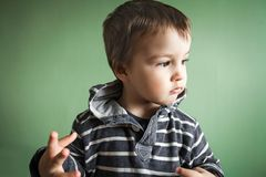 Little cute boy in pullover showing gesture. Little cute handsome thoughtful boy in stripped pullover showing gesture Royalty Free Stock Photos