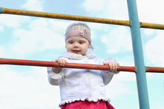 Little cute happy girl in hat climbs on ladder Stock Photo