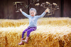 Little cute happy girl having fun with hay on a farm Royalty Free Stock Photo