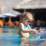 Little cute happy girl in swimming pool during Stock Photos