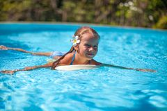 Little cute happy girl swims in the swimming pool Stock Images