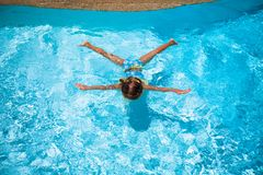 Little cute happy girl swims in the swimming pool Stock Photo