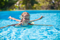 Little cute happy girl swims in the swimming pool Stock Image
