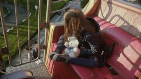 Little cute happy girl with toy bear looking at the park from the high. She travels on a kid train stock video footage