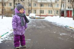 Little cute happy girl walking in the snow on a Stock Images
