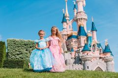 Little adorable girls in beautiful princess dress at fairy-tale park. Little cute happy girls in beautiful princess at fairy-tale park royalty free stock image