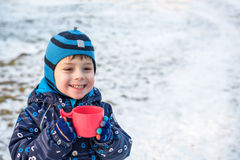 Little cute kid boy with cup of steaming hot chocolate or children punch. Happy child play in winter forest outdoors Royalty Free Stock Photography