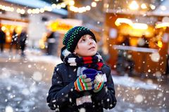 Little cute kid boy drinking hot children punch or chocolate on German Christmas market. Happy child on traditional. Family market in Germany, Laughing boy in stock images