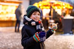 Little cute kid boy eating German sausage and drinking hot children punch on Christmas market. Happy child on royalty free stock photos