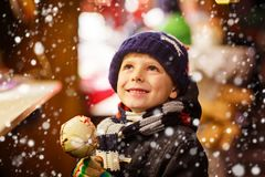 Little kid boy eating sugar apple sweets stand on Christmas market Royalty Free Stock Images