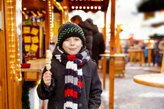 Little cute kid boy eating white chocolate covered fruits on skewer on traditional German Christmas market. Happy child stock images