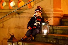 Little cute kid boy with with a light lantern on stairs near church. Royalty Free Stock Photo