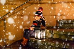 Little cute kid boy with with a light lantern on stairs near church. Happy child on Christmas market in Germany. Kid stock image