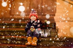 Little cute kid boy with with a light lantern on stairs near church. Happy child on Christmas market in Germany. Kid waiting on parents on cold winter day Royalty Free Stock Photos