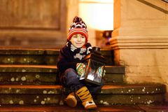 Little cute kid boy with with a light lantern on stairs near church. Happy child on Christmas market in Germany. Kid waiting on parents on cold winter day Royalty Free Stock Image
