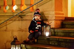 Little cute kid boy with with a light lantern on stairs near church. Happy child on Christmas market in Germany. Kid waiting on parents on cold winter day Stock Photos