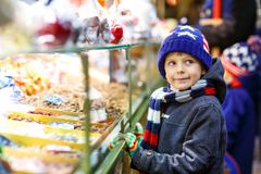 Little kid boy with gingerbread and sweets stand on Christmas market Royalty Free Stock Image