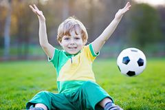 Little cute kid boy of 4 playing soccer with football on field, outdoors Royalty Free Stock Images