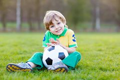 Little cute kid boy of 4 playing soccer with football on field, outdoors Royalty Free Stock Image