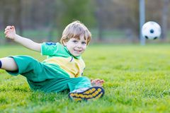Little cute kid boy of 4 playing soccer with football on field, outdoors Stock Photos