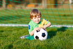 Little cute kid boy of 4 playing soccer with football on field, outdoors Royalty Free Stock Photos