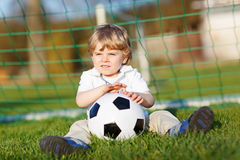 Little cute kid boy of 4 playing soccer with football on field, outdoors Stock Photo