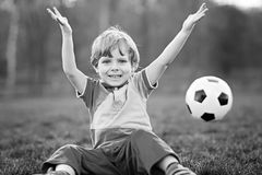 Little cute kid boy of 4 playing soccer with football on field, outdoors Stock Image