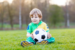 Little cute kid boy of 4 playing soccer with football on field, outdoors Stock Images