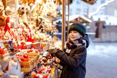 Little cute kid boy selecting decoration on Christmas market. Beautiful child shopping for toys and decorative ornaments royalty free stock photo