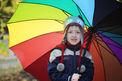 Little cute kid boy walking with big umbrella outdoors on rainy day. Child having fun and wearing colorful waterproof clothes and. Cap, kids concept Stock Photos