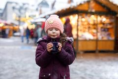 Little cute kid girl with cup of steaming hot chocolate or children punch. Happy child on Christmas market in Germany. Traditional leisure for families on xmas stock image