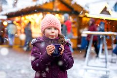 Little cute kid girl with cup of steaming hot chocolate or children punch. Happy child on Christmas market in Germany. Traditional leisure for families on xmas royalty free stock image