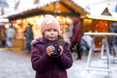 Little cute kid girl with cup of steaming hot chocolate or children punch. Happy child on Christmas market in Germany. Traditional leisure for families on xmas stock photos