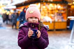Little kid girl with hot chocolate on Christmas market. Little cute kid girl with cup of steaming hot chocolate or children punch. Happy child on Christmas stock images