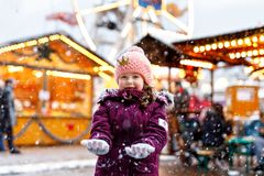 Little cute kid girl having fun on traditional Christmas market during strong snowfall. Happy child enjoying traditional. Family market in Germany. Laughing stock photo