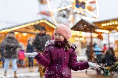 Little cute kid girl having fun on traditional German Christmas market during strong snowfall.. Happy child enjoying. Traditional family market in Germany stock images