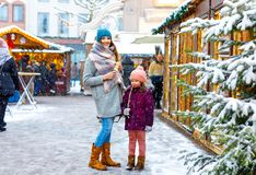 Little cute kid girl and young mother having fun on traditional German Christmas market during strong snowfall. Happy child and beautiful women enjoying family royalty free stock images